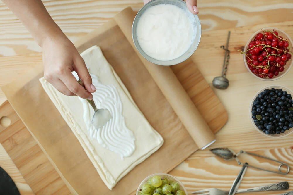 Woman making berry dessert, top view