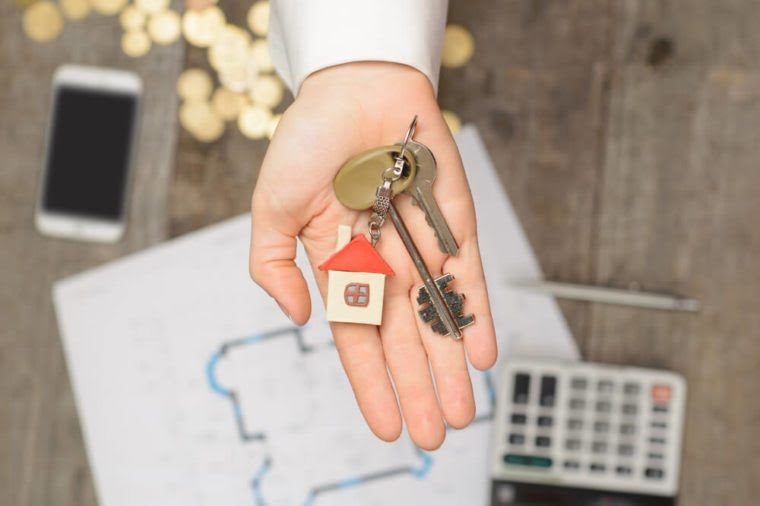 Real estate agent handing over a house key, desktop with tools, wood swatches and computer on background, top view